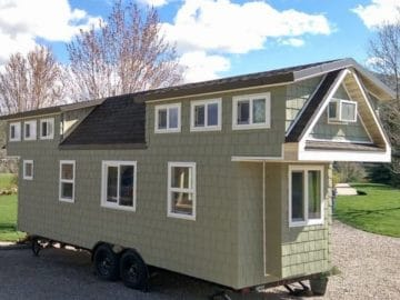 Side of light green tiny home with white trim