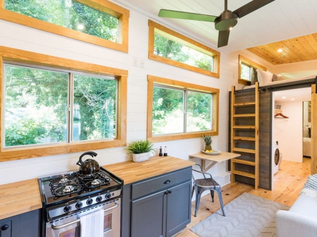 Large windows in tiny home wall above kitchen counter with stainless steel gas stove