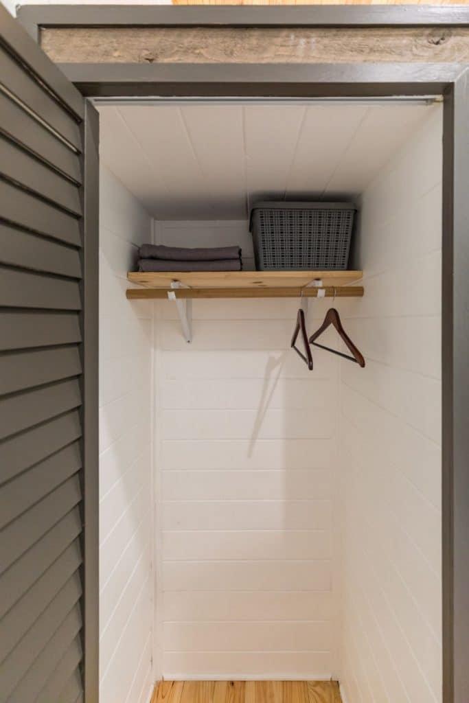 Closet with dark shutter door open showing hanger on rod