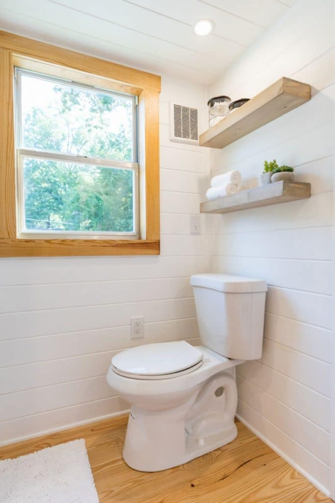 White traditional toilet against white wall under wood trim window
