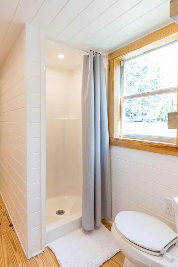 Shower stall with curtain next to window in hall