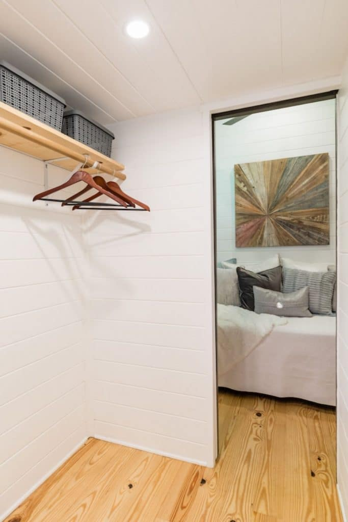 Closet space looking into bedroom with white walls