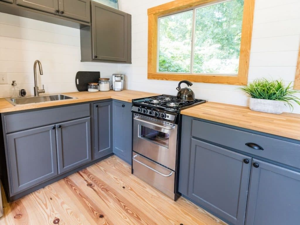Blue cabinets in L shaped kitchen with butcher block countertop