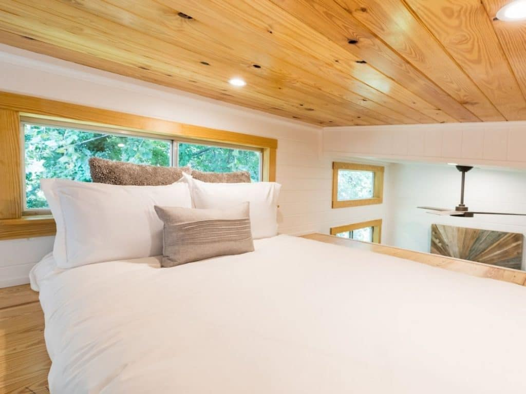Loft with white bed and light wood ceiling panels