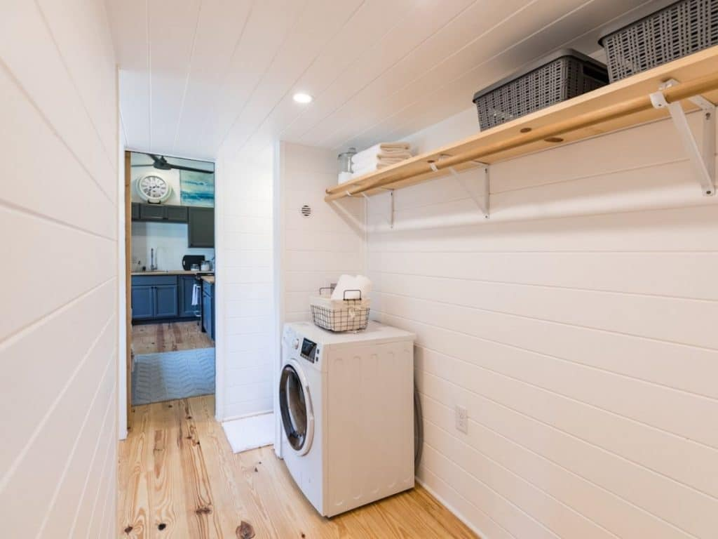 Combination washer and dryer against white wall under closet rod