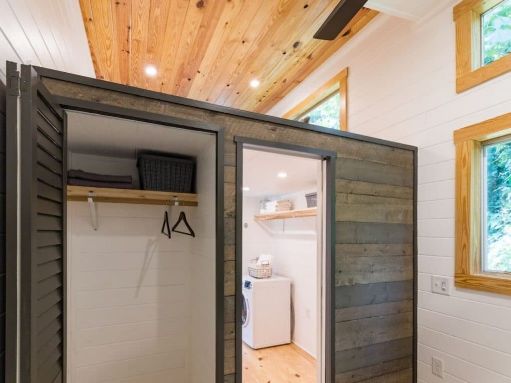 View of open closet door and bathroom with laundry against whit ewall