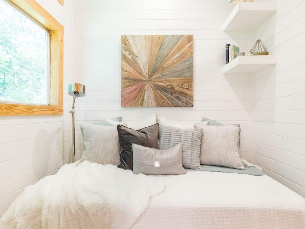 Bed against white wall with earth tone painting above bed