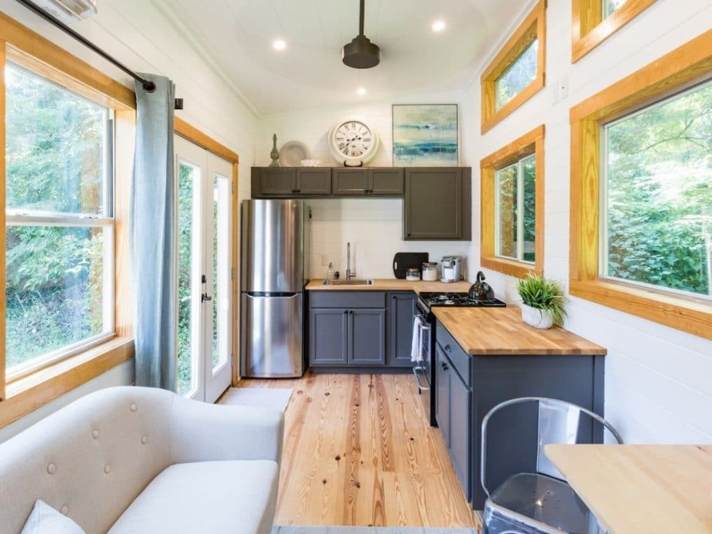 View into tiny home kitchen with navy cabinets and butcherblock counter