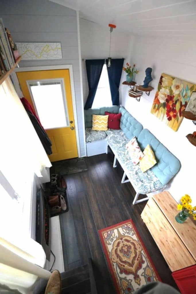 Tiny house view from loft showing couch in corner living room nook
