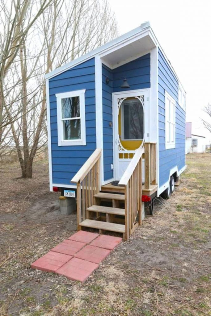 Front of tiny house with small porch blue siding and yellow door