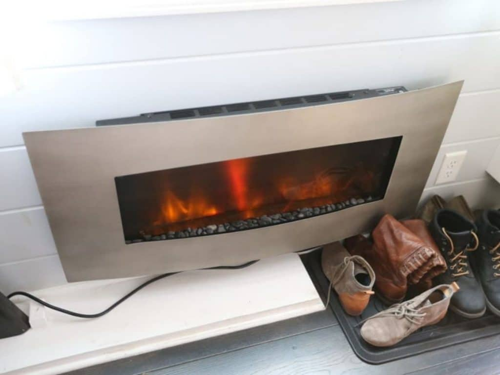 Wall mounted fireplace in tiny home with boots beside it