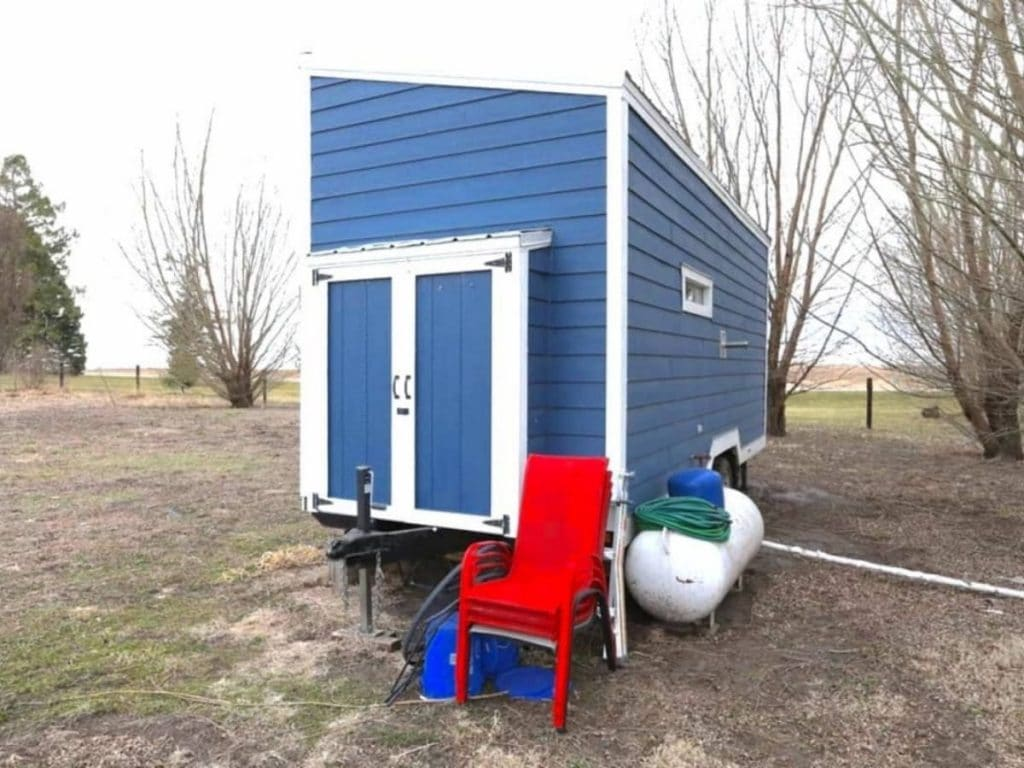 Back of blue tiny house with white trim