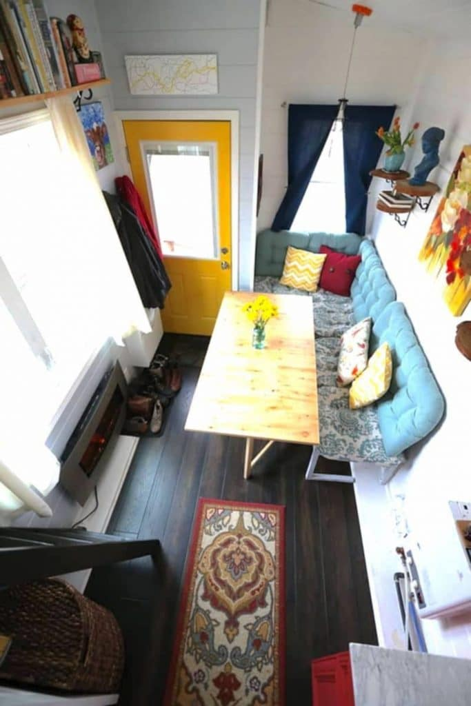 Teal sofa with wooden table in front next to yellow front door of tiny home