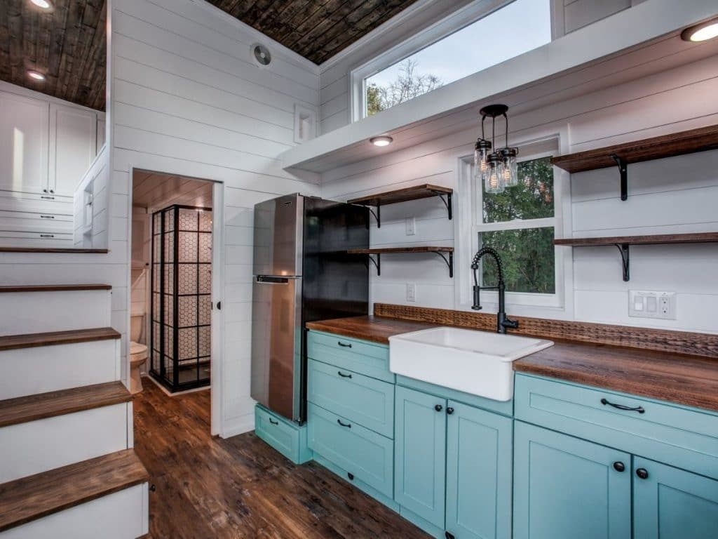 Kitchen with light teal cabinets and dark wood counters