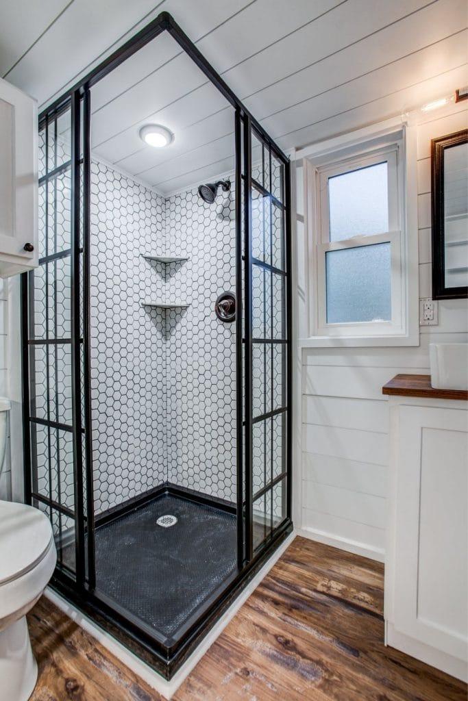 Open shower stall in corner of tiny bathroom