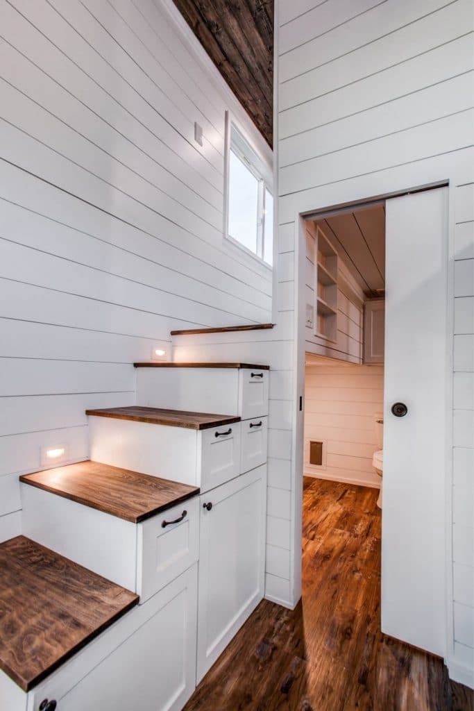 White and wood stairs to loft by door into bathroom