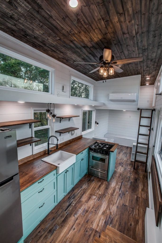 View of tiny house kitchen and living space from loft stairs