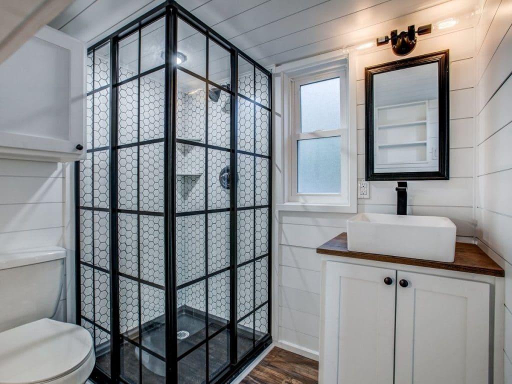 Bathroom vanity next to black door style shower stall