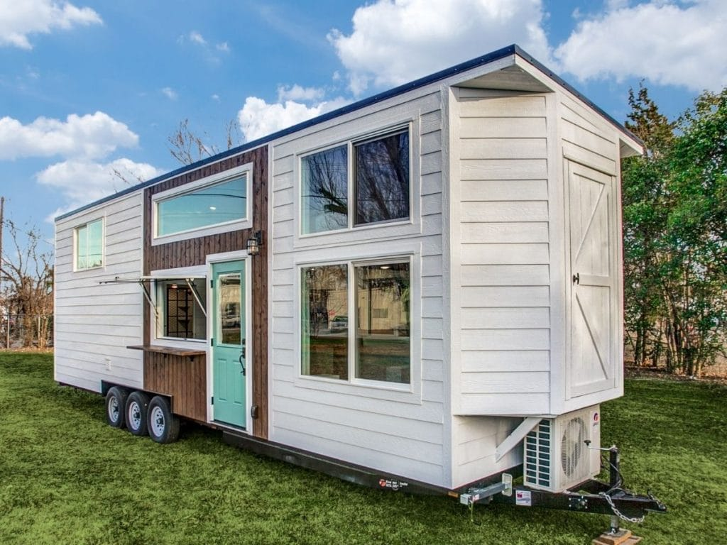 White siding on tiny house with teal door and wood accents
