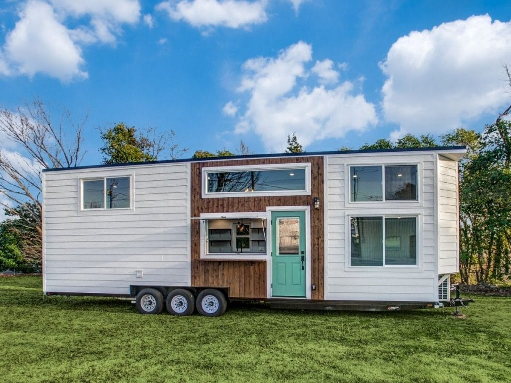 White tiny house on wheels sitting in grassy field with blue skies