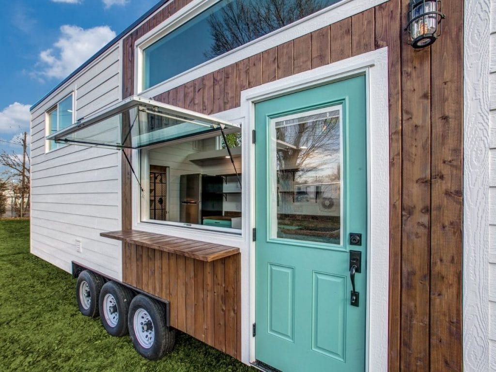 Teal front door in wood siding with large open window