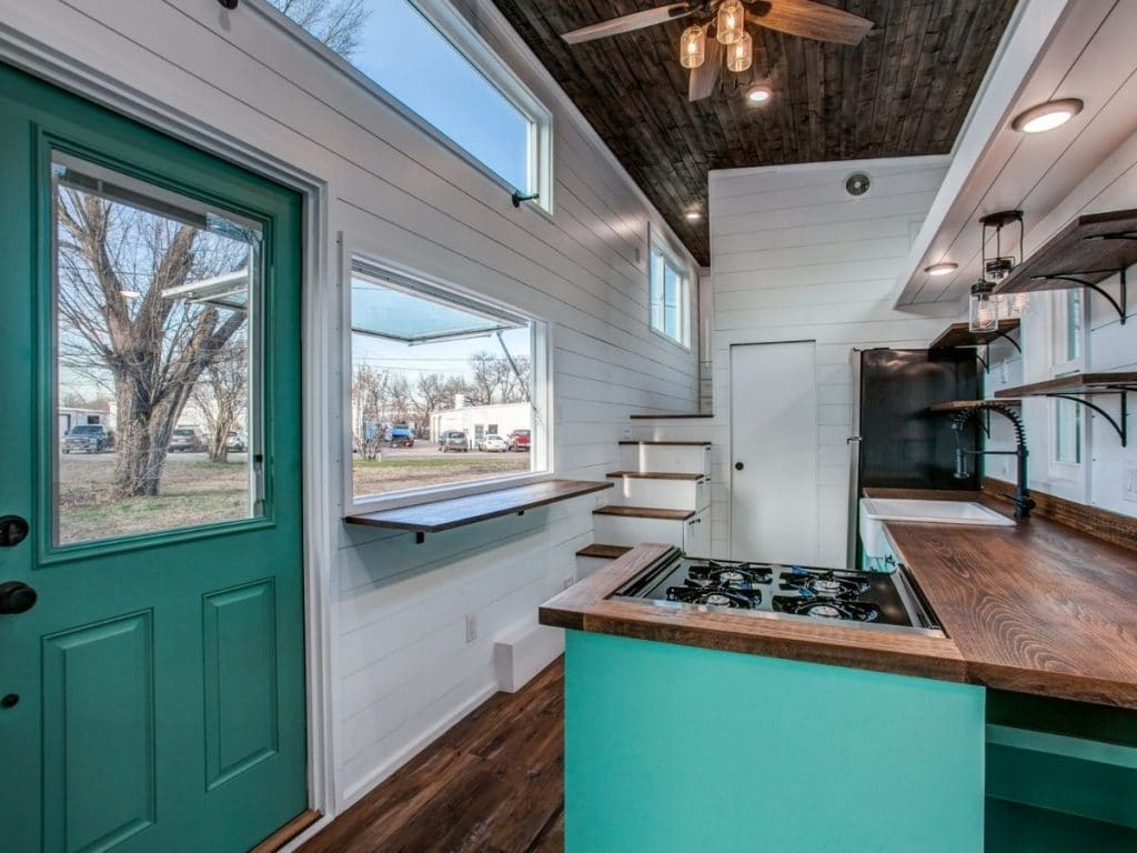 View into teal and white tiny kitchen with gas cooktop