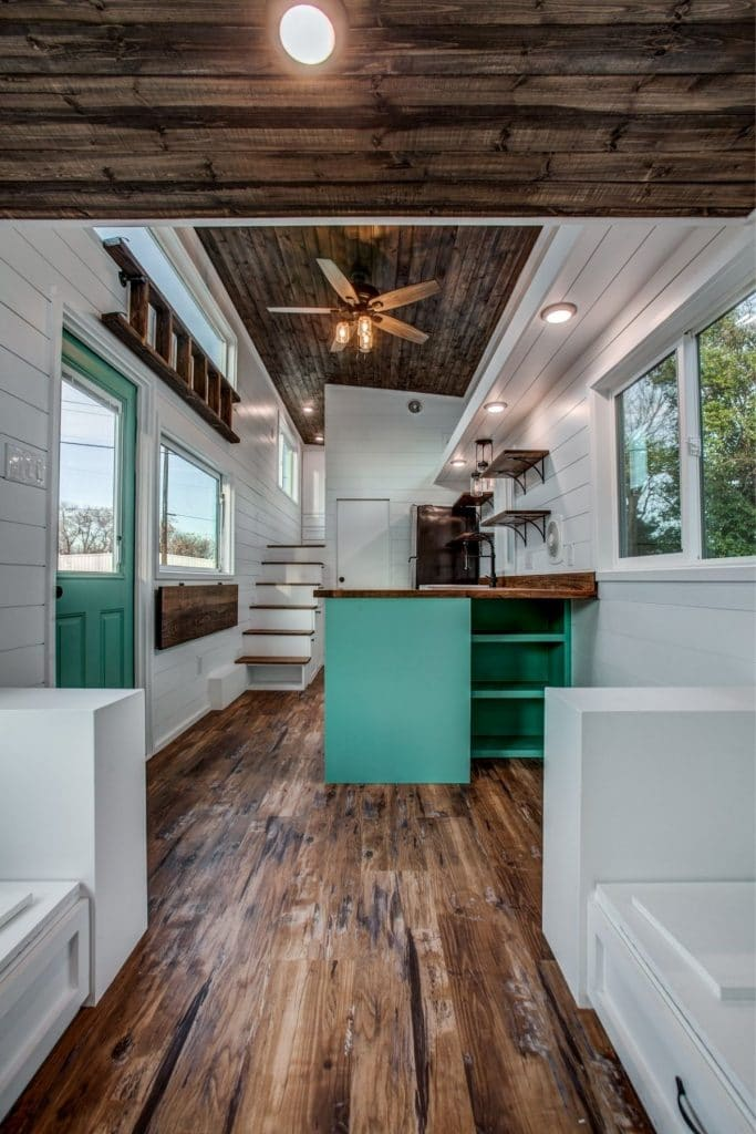 Teal kitchen cabinets with white walls and dark wood ceiling