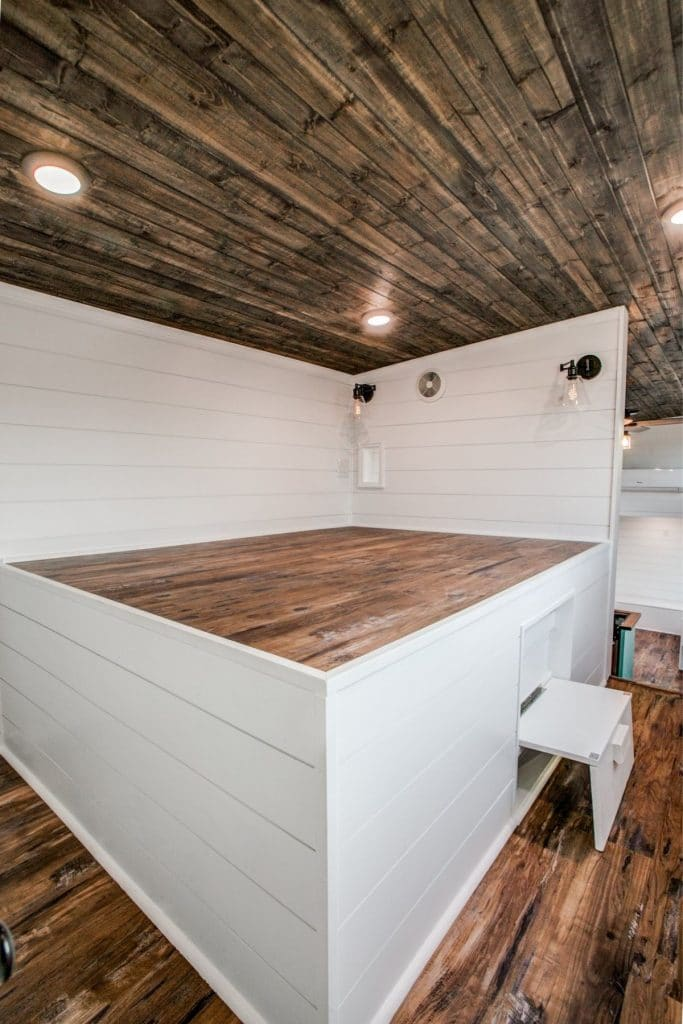White platform bed in tiny house bedroom with drawers underneath