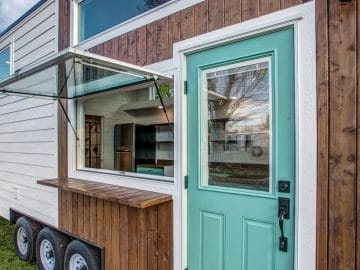 Teal front door of tiny house next to window with small ledge