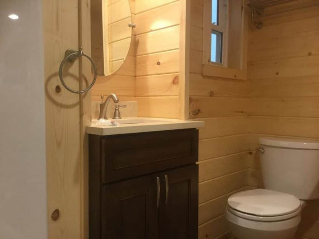 View into tiny bathroom with dark wood vanity and white counter
