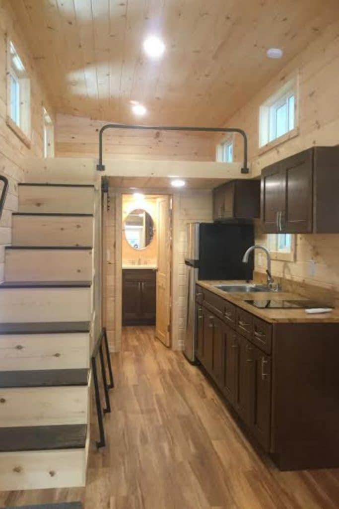 Stairs and kitchen inside tiny house with natural wood