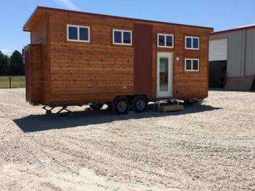 Cabin style tiny house on wheels in gravel lot