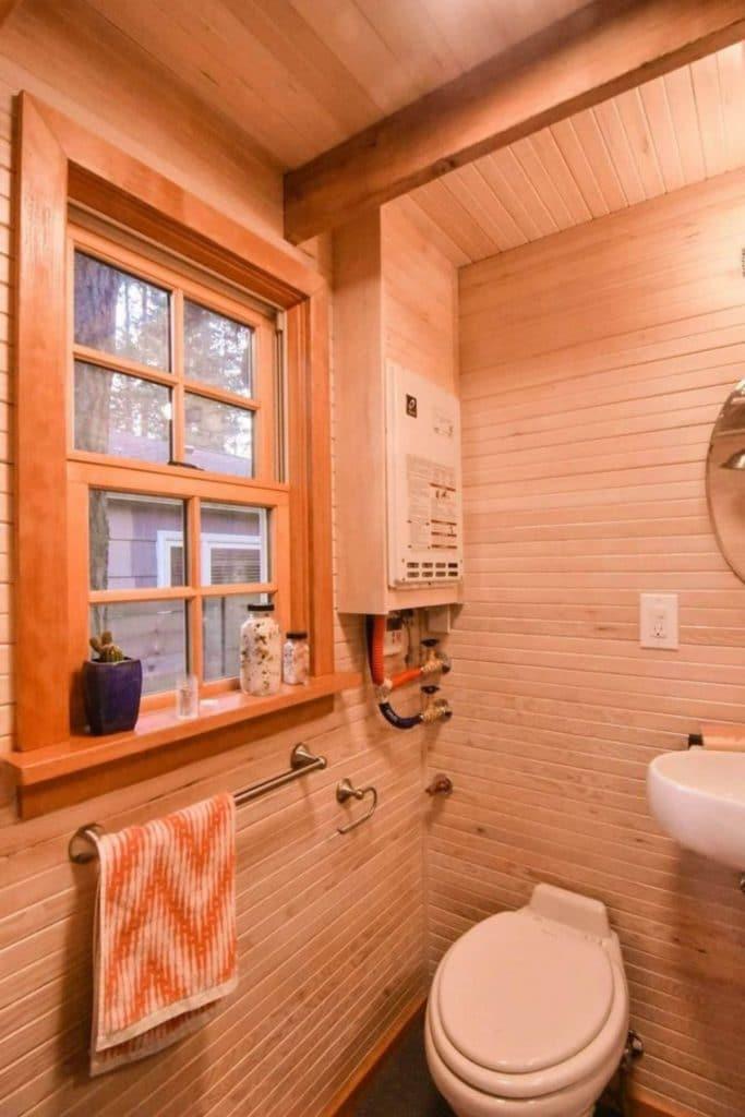 Toilet in wood lined bathroom with towel hanger below window