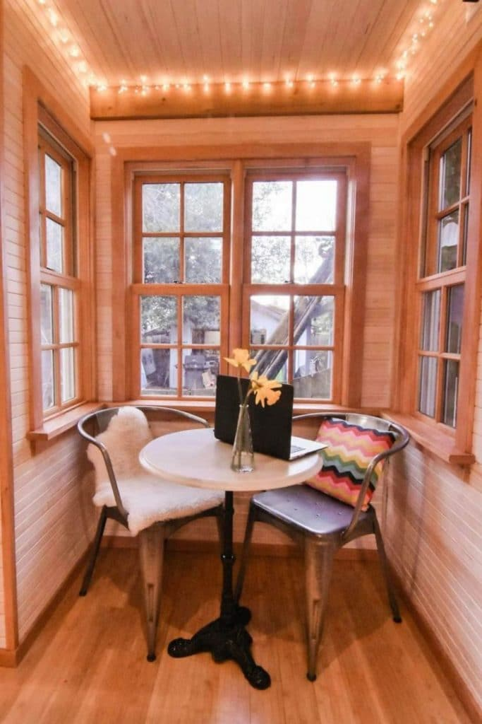 Corner breakfast nook with small round white table and bay windows