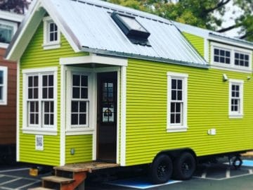Neon green tiny home with white trim on lot