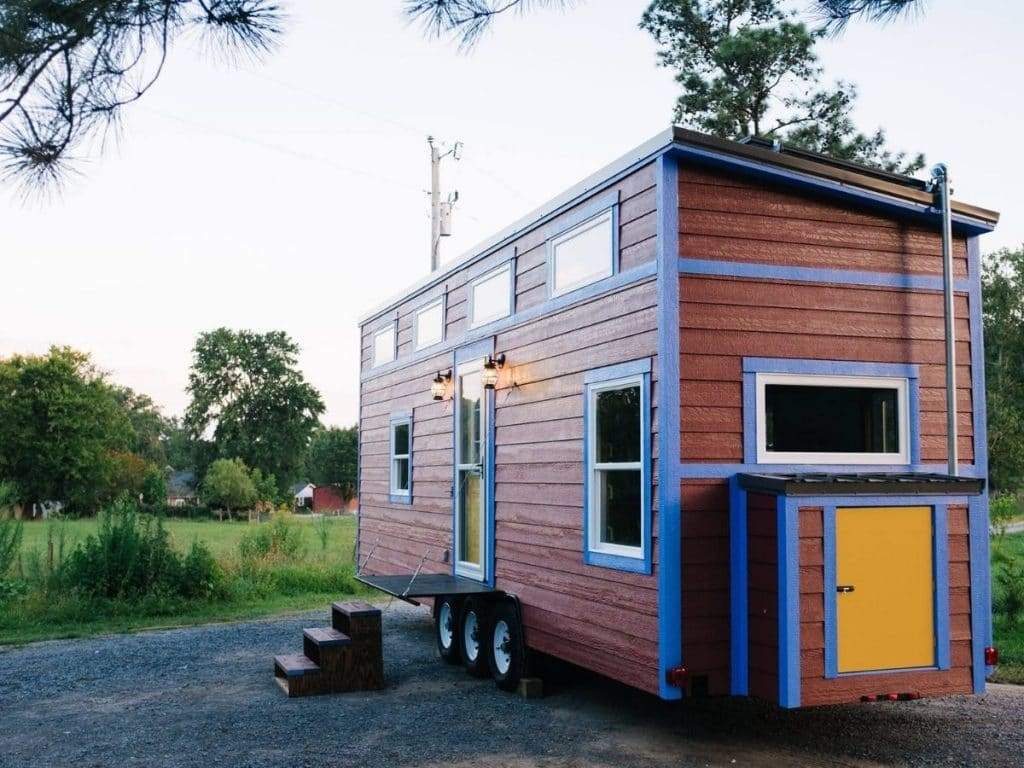 Red and bleu tiny home with yellow door on end of house