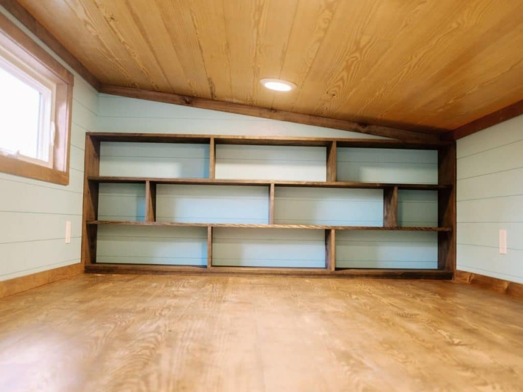 Built-in shelves against blue wall in loft