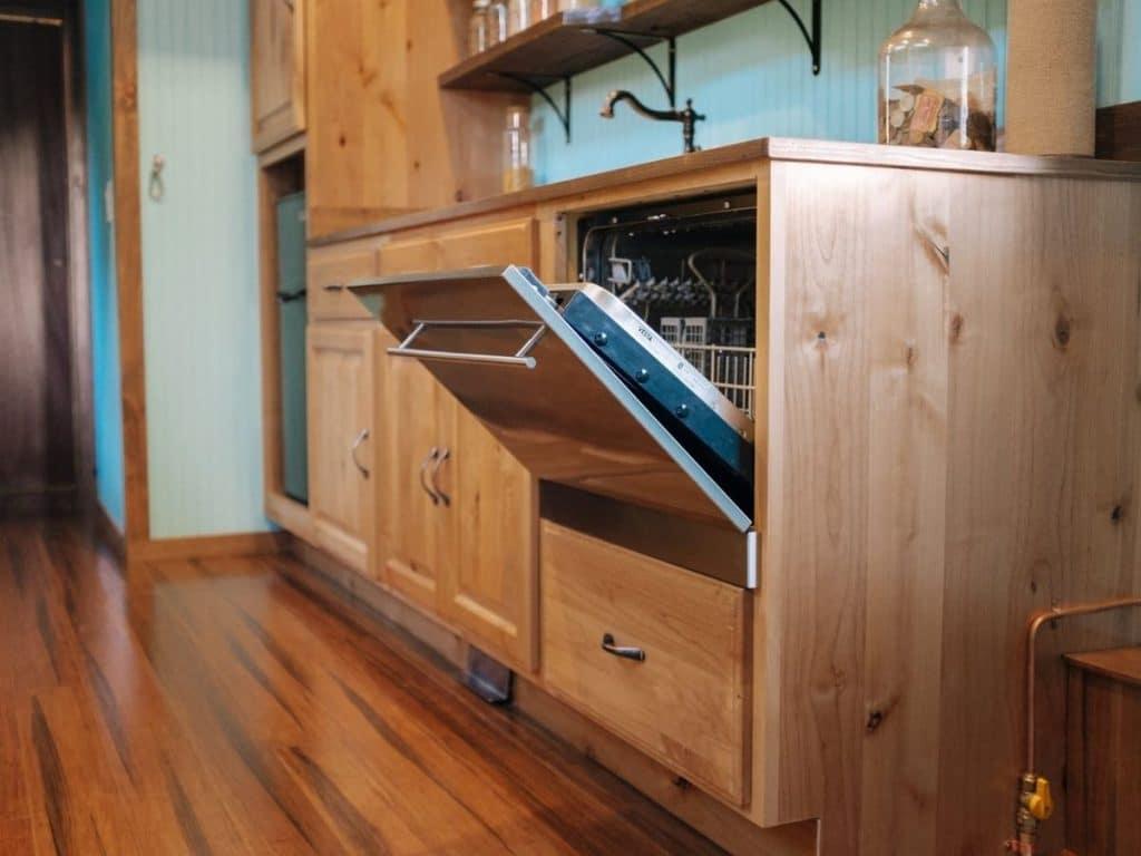 Dishwasher door open with wood panel finish