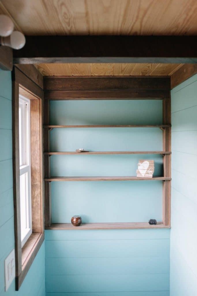 Shelves on wall in tiny house bathroom