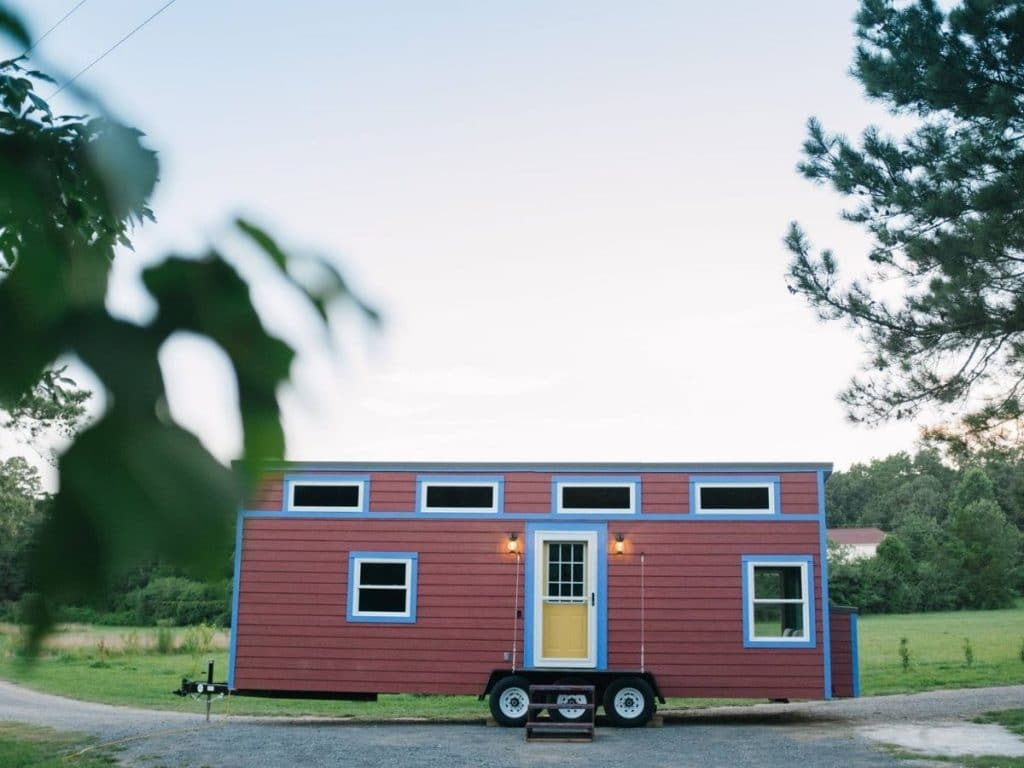 Red and blue tiny house parked with grass in background