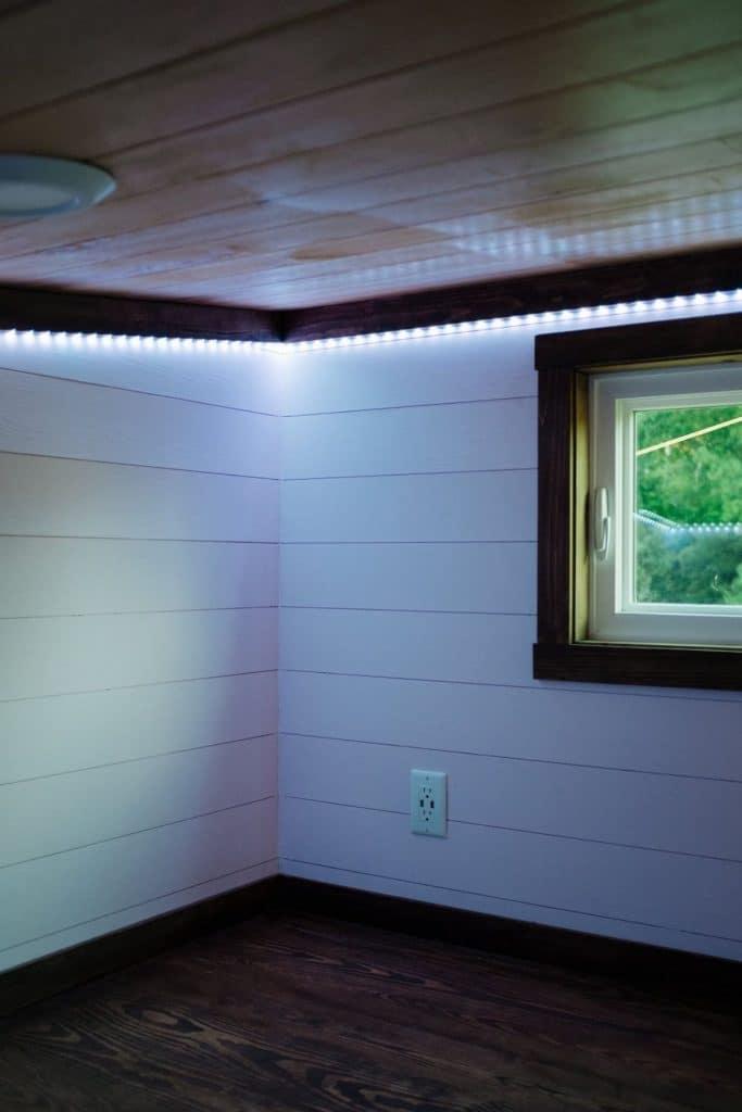 Loft space with white shiplap and dark wood trim around edges