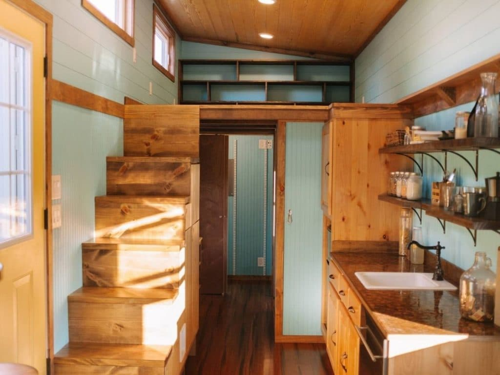 TIny house living space with stairs on one side and kitchen on opposite side