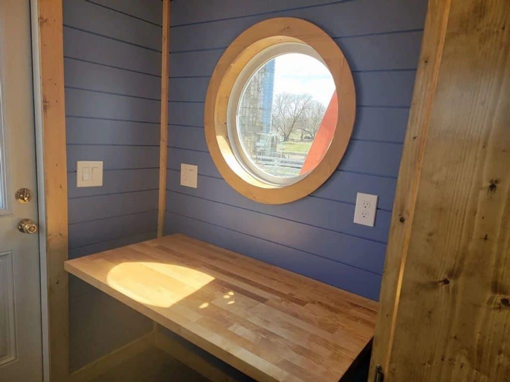 Wooden work space inside door with round window above