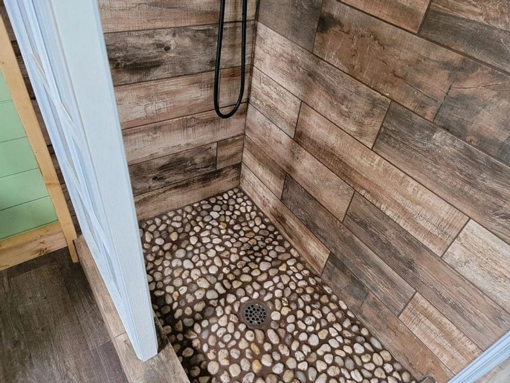 Pebble bottom of shower with wood wall