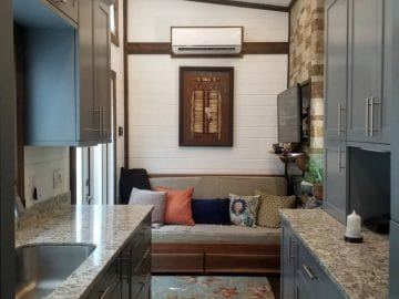 Sofa against back wall with granite counter and gray cabinets in foreground
