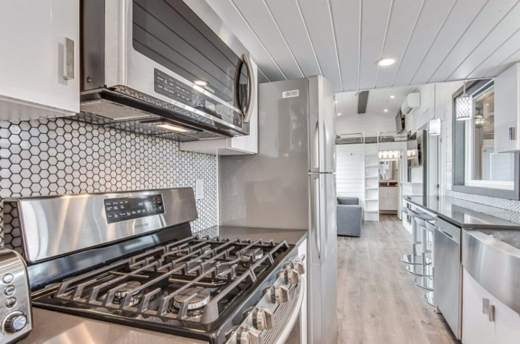 Gas burner stove in kitchen with microwave vent hood