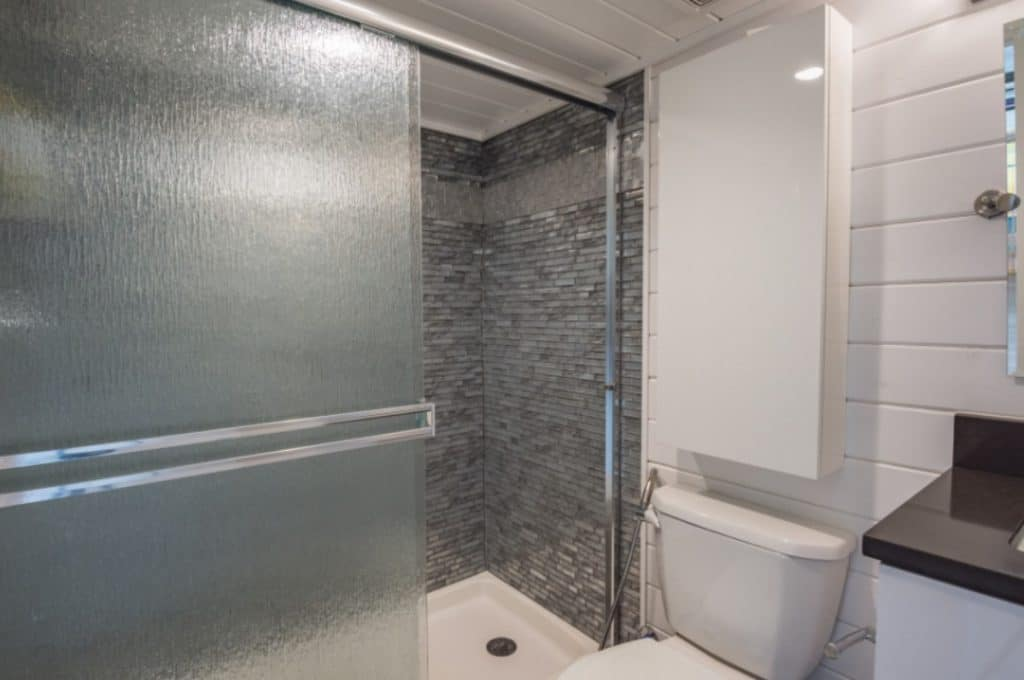 Gray tiled shower in tiny house bathroom with glass door