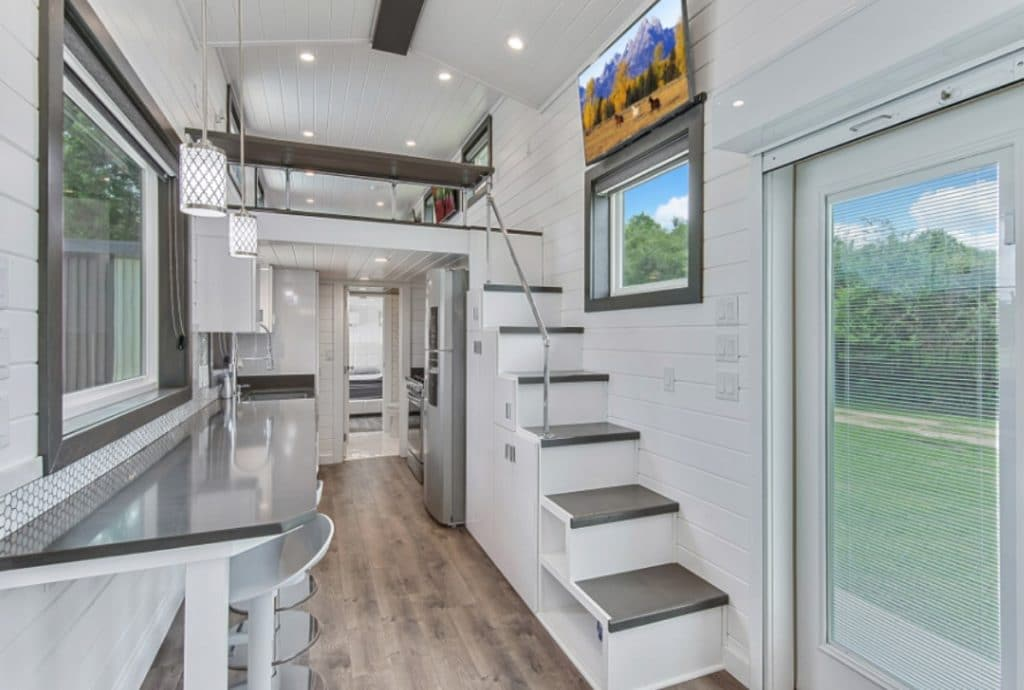 White interior with glass door and stairs to loft