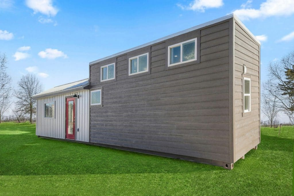 Converted container tiny house with gray siding in grassy field