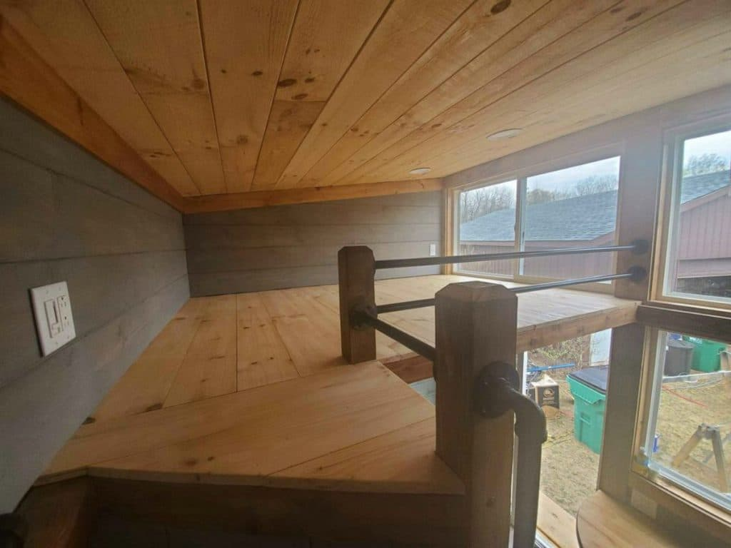 Loft with large railing and wooden base
